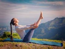 Woman doing Ashtanga Vinyasa Yoga asana Navasana - boat pose Royalty Free Stock Image