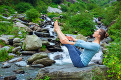 Woman doing Ashtanga Vinyasa Yoga asana Navasana outdoors. Yoga outdoors - young sporty fit woman doing Ashtanga Vinyasa Yoga asana Navasana - boat pose - in Royalty Free Stock Image