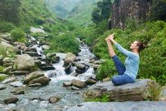 Woman doing Ashtanga Vinyasa Yoga asana outdoors. Yoga exercise outdoors -  woman doing Ashtanga Vinyasa Yoga balance asana Ubhaya padangusthasana Big Double Toe Stock Photo