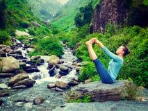 Woman doing Ashtanga Vinyasa Yoga asana outdoors Royalty Free Stock Photo