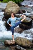 Woman doing Ashtanga Vinyasa Yoga asana outdoors at waterfall Stock Images