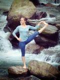 Woman doing Ashtanga Vinyasa Yoga asana outdoors at waterfall Royalty Free Stock Photography