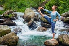 Woman doing Ashtanga Vinyasa Yoga asana outdoors at waterfall. Yoga outdoors - woman doing Ashtanga Vinyasa Yoga balance asana Utthita Hasta Padangushthasana Stock Photos