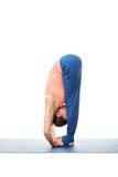 Woman doing Ashtanga Vinyasa Yoga asana Padahastasana. Standing forward bend with hand under feet pose posture isolated on white background Stock Photography