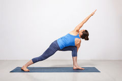 Woman doing Ashtanga Vinyasa yoga asana Parivrtta parsvakonasana. Revolved side angle pose on yoga mat on yoga mat in studio on grey bagckground stock photo