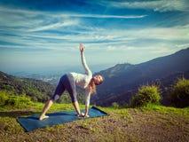 Woman doing Ashtanga Vinyasa yoga asana Parivrtta trikonasana Stock Image