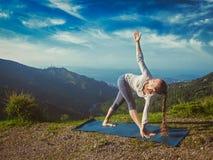 Woman doing Ashtanga Vinyasa yoga asana Parivrtta trikonasana Royalty Free Stock Images