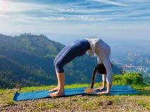 Woman doing Ashtanga Vinyasa Yoga asana Urdhva Dhanurasana outdoors Royalty Free Stock Image