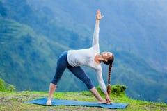 Woman doing Ashtanga Vinyasa yoga asana Utthita trikonasana. Extended triangle pose outdoors Stock Image