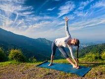 Woman doing Ashtanga Vinyasa yoga asana Utthita trikonasana Stock Image