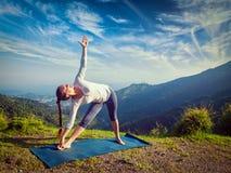 Woman doing Ashtanga Vinyasa yoga asana Utthita trikonasana. Extended triangle pose outdoors in mountains in the morning. Vintage retro effect filtered Stock Photos