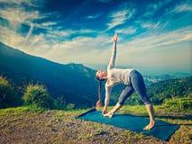 Woman doing Ashtanga Vinyasa yoga asana Utthita trikonasana Stock Photography