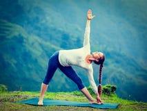 Woman doing Ashtanga Vinyasa yoga asana Utthita trikonasana Royalty Free Stock Photo