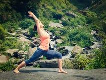 Woman doing Ashtanga Vinyasa Yoga asana Virabhadrasana 1 Warrior Stock Photography