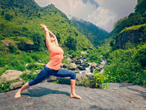 Woman doing Ashtanga Vinyasa Yoga asana Virabhadrasana 1 Warrior Royalty Free Stock Photo