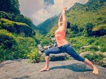 Woman doing Ashtanga Vinyasa Yoga asana Virabhadrasana 1 Warrior Stock Image