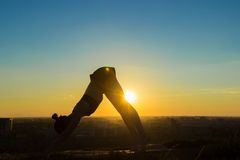 Woman doing Ashtanga yoga in the park at sunset. Silhouette of sporty woman doing Ashtanga yoga in the park at sunset. Sunset light, sun lens flares, golden hour Royalty Free Stock Image