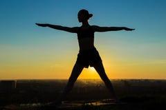Woman doing Ashtanga yoga in the park at sunset. Silhouette of sporty woman doing Ashtanga yoga in the park at sunset. Sunset light, sun lens flares, golden hour Stock Image