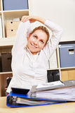 Woman doing back training in office. Smiling young business woman doing back training at her desk in the office Stock Photography