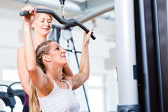 Woman doing back training with trainer in gym Royalty Free Stock Images