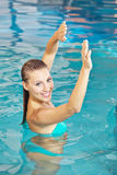Woman doing back training in water. In aqua fitness class Stock Photography