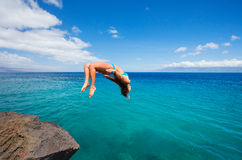 Woman doing backflip into ocean Royalty Free Stock Image
