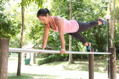 Woman doing balancing exercise on exercise bar in park Stock Images