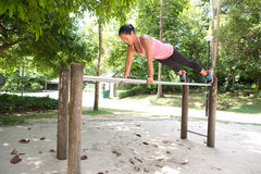 Woman doing balancing exercise on exercise bar in park Royalty Free Stock Photo