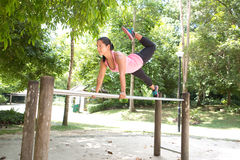 Woman doing balancing exercise on exercise bar in park Royalty Free Stock Images