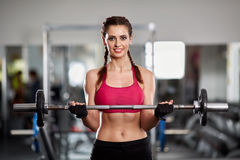 Woman doing barbell biceps curl Stock Photography