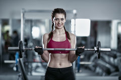 Woman doing barbell biceps curl. Young woman doing barbell curl, biceps workout stock photo