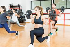 Woman Doing Barbell Lunges With Friends In Health Club royalty free stock photography