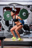 Woman doing barbell squats. Young woman doing squats with barbell in the gym Stock Photography