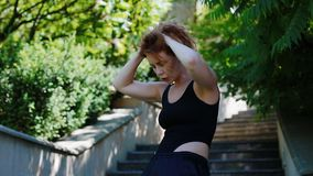 Woman doing bearhing exercise outdoors. The athlete holds his hands behind his head and twists stock video footage