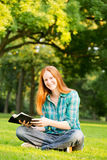 A Woman Doing Bible Study in a Park Stock Images