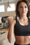 Woman doing bicep curls with dumbbells at a gym, vertical Royalty Free Stock Photo