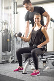 Woman doing bicep curls in gym with her personal trainer. Young adult women working out in gym, doing bicep curls with help of her personal trainer Stock Photos