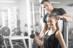 Woman doing bicep curls in gym with her personal trainer Royalty Free Stock Images