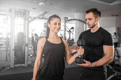 Woman doing bicep curls in gym with her personal trainer Stock Images