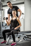 Woman doing bicep curls in gym with her personal trainer. Young adult women working out in gym, doing bicep curls with help of her personal trainer Stock Photo