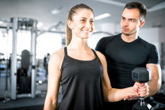 Woman doing bicep curls in gym with her personal trainer. Young adult women working out in gym, doing bicep curls with help of her personal trainer Royalty Free Stock Photography