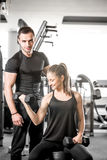 Woman doing bicep curls in gym with her personal trainer. Young adult women working out in gym, doing bicep curls with help of her personal trainer Royalty Free Stock Photo