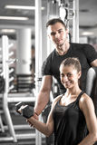 Woman doing bicep curls in gym with her personal trainer. Young adult women working out in gym, doing bicep curls with help of her personal trainer Royalty Free Stock Images