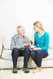 Woman doing blood glucose monitoring for senior man. Young women doing blood glucose monitoring for senior men at home Royalty Free Stock Photography