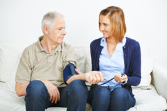 Woman doing blood pressure monitoring for patient Royalty Free Stock Images