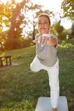 Woman doing body balance exercise outdoor Stock Photos