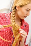Woman doing braid on blonde hair. Fancy trendy blond hairstyle at home concept. Woman wearing pink pajamas doing braid on blonde hair Stock Photos