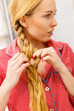 Woman doing braid on blonde hair Royalty Free Stock Photo