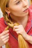 Woman doing braid on blonde hair Royalty Free Stock Image