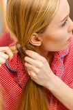 Woman doing braid on blonde hair. Fancy trendy blond hairstyle at home concept. Woman wearing pink pajamas doing braid on blonde hair Stock Photo